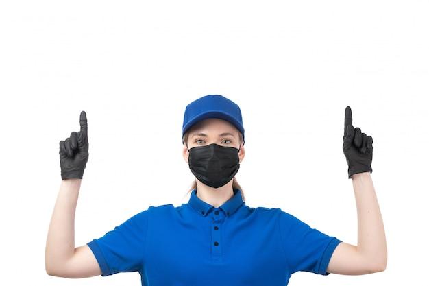 Eine junge weibliche kurierin der vorderansicht in blauen einheitlichen schwarzen handschuhen und in der schwarzen maske, die aufwirft
