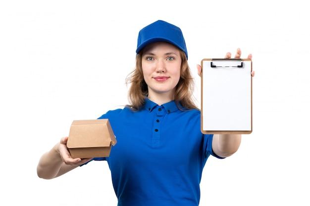 Eine junge weibliche kurierin der vorderansicht in der blauen kappe des blauen hemdes lächelnd, die lebensmittelpaket und notizblock auf weiß hält