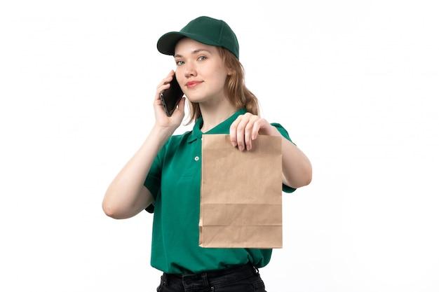 Eine junge weibliche kurierin der vorderansicht in der grünen uniform lächelnd, die lebensmittelpaket hält, während sie am telefon spricht