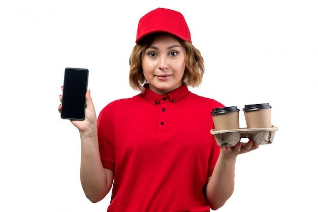 Eine junge weibliche kurierin der vorderansicht in der roten kappe des roten hemdes, die smartphone und kaffeetassen hält