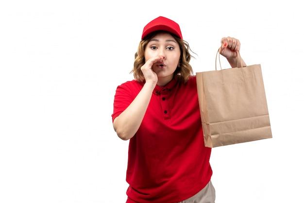 Eine junge weibliche kurierin der vorderansicht in der uniform, die das flüstern des lebensmittellieferpakets hält