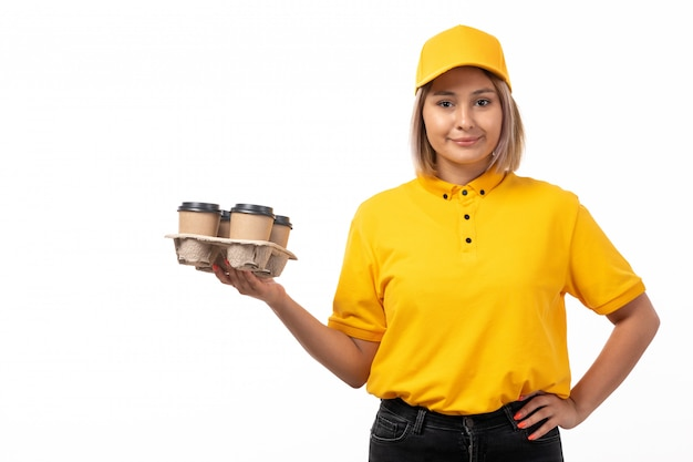 Eine junge weibliche kurierin der vorderansicht in gelber gelber hemdkappe und schwarzen jeans, die kaffeetassen lächelnd halten