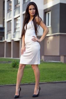 Eine junge wunderschöne frau in einem schönen kleid geht eine stadtstraße entlang