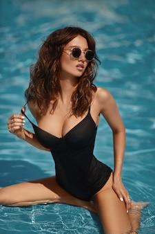 Eine junge wunderschöne frau mit sexy großen brüsten und schlanker taille in einem schwarzen badeanzug, der im schwimmbad draußen an einem sommertag aufwirft