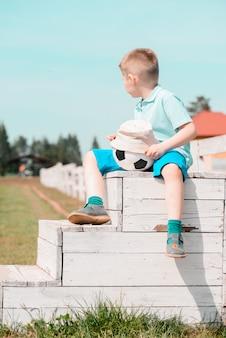 Eine jungencheerleader sitzt mit einem fußball auf dem feld auf dem bankaufpassenden fußball.