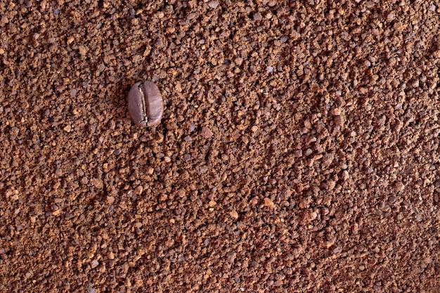 Eine kaffeebohne auf einem hintergrund aus gemahlenem kaffee, kaffeepulver