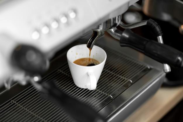 Eine kaffeemaschine gießt frisch gebrühten heißen kaffee in eine weiße tasse