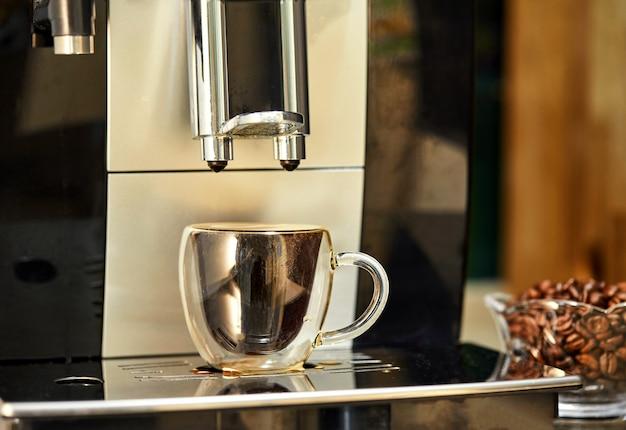 Eine kaffeemaschine macht espresso in einer transparenten tasse. frisch gebrühter kaffeekonzept