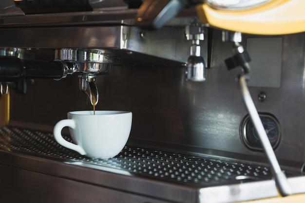 Eine kaffeetasse mit kaffeemaschine in der kaffeestube.