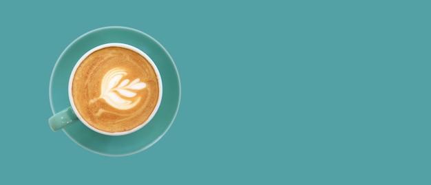 Eine kaffeetasse mit latte art auf grüner oberfläche, draufsicht, banner