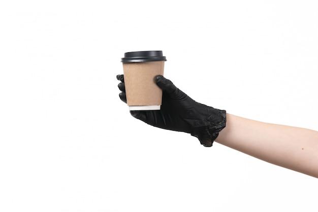 Eine kaffeetasse mit vorderansicht, die von einer frau in schwarzen handschuhen gehalten wird