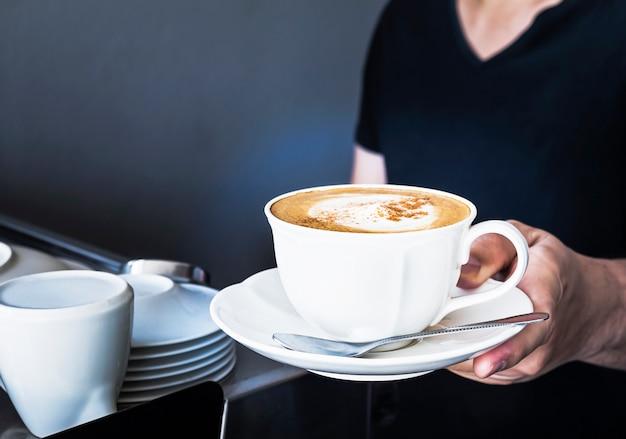 Eine kaffeetasse wird von barista im teilweise dunklen raumladen serviert