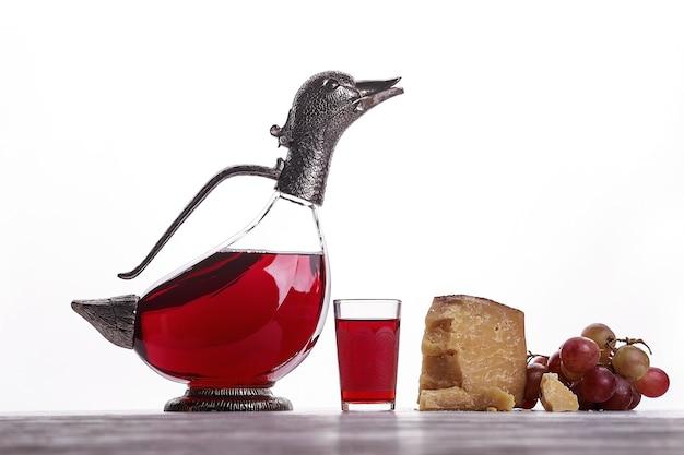 Eine karaffe rotwein, ein glas wein, teurer käse, schimmelkäse, schwarzkäse und trauben. auf weißem hintergrund. platz für logo.