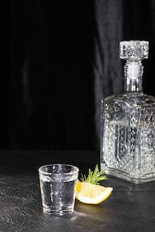 Eine karaffe und ein kleines glas wodka oder ein anderes farbloses alkoholisches getränk auf schwarzem hintergrund