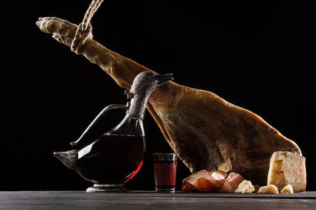 Eine karaffe wein in form einer ente, ein glas wein, eine bein parmaschinken und käse. schwarzer hintergrund.