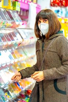 Eine kaukasische brünette mit einer maske, die gummibärchen in einer konditorei kauft. erste spaziergänge der unkontrollierten covid-19-pandemie