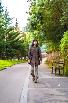 Eine kaukasische brünette mit kurzen haaren und einer schutzmaske für das coronavirus. erste spaziergänge der unkontrollierten covid-19-pandemie