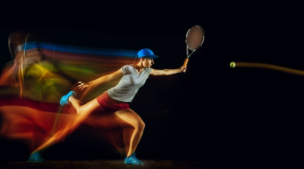 Eine kaukasische frau, die tennis spielt, isoliert auf schwarzer wand in gemischtem und stobe licht. fit junge spielerin in bewegung oder aktion während des sportspiels. konzept von bewegung, sport, gesundem lebensstil.
