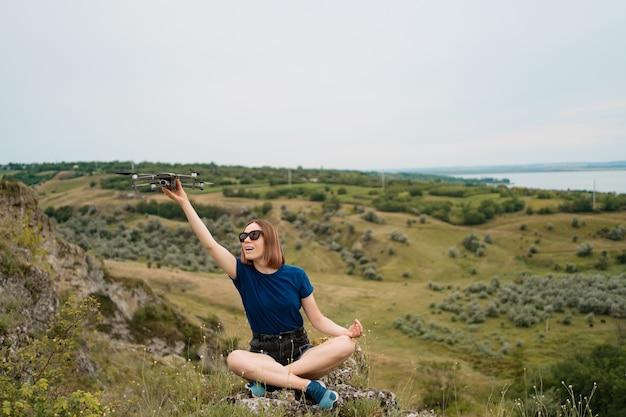 Eine kaukasische frau mit einer drohne in der hand, sitzend auf einem grünen felsigen hügel mit himmel