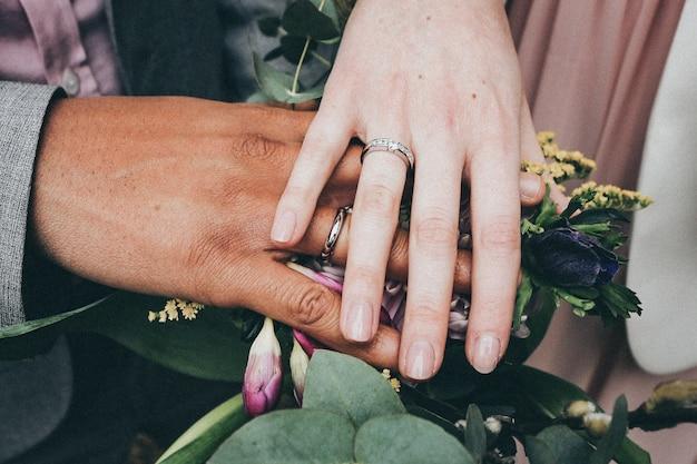 Eine kaukasische frau und ein afroamerikanischer mann, die ringe tragen und blumen halten