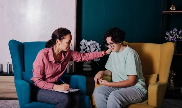 Eine kaukasische psychologin sitzt auf einem stuhl und umarmt die schultern einer patientin im teenageralter