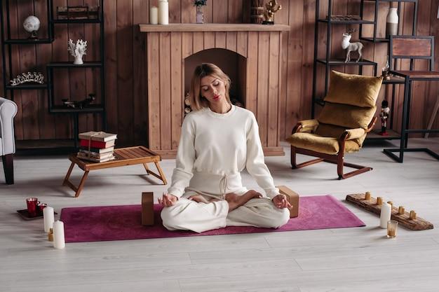 Eine kaukasische ruhige frau in weißem baumwoll-yoga-anzug, die im lotussitz auf rosa yogamatte mit gekreuzten beinen sitzt. kerzen umringen sie auf dem boden. gemütliches modernes holzinterieur.