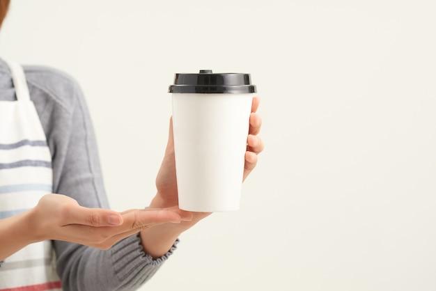 Eine kellnerin, die eine papptasse heißen kaffee im café hält und serviert
