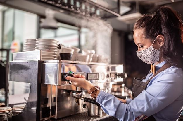 Eine kellnerin mit gesichtsmaske betreibt eine kaffeemaschine in einem café.