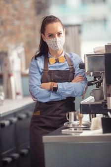 Eine kellnerin mit gesichtsmaske steht in einer bar neben einer kaffeemaschine mit den armen auf der brust.