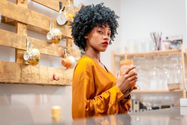 Eine kellnerin modelliert einen orangensaft, der kunden anlächelt