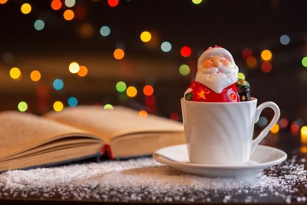 Eine keramikfigur des weihnachtsmanns sitzt in einer weißen tasse.