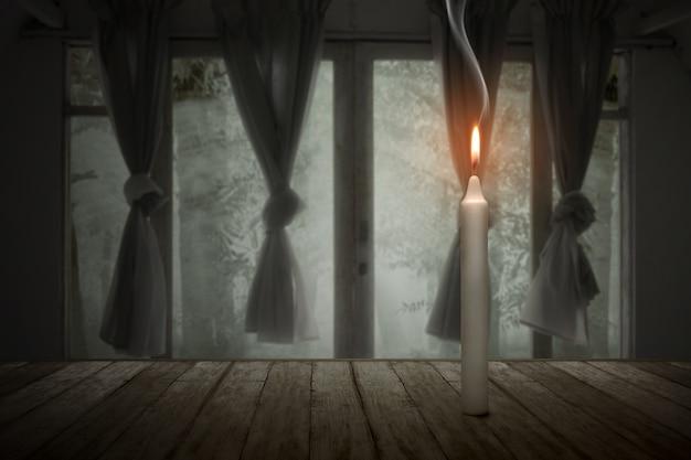 Eine kerze, die in einem verlassenen haus halloween-konzept brennt