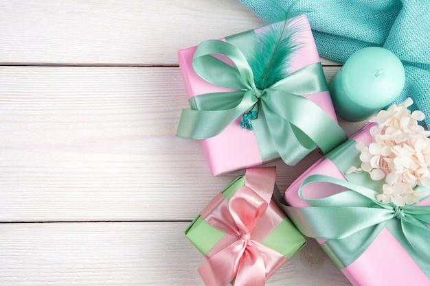 Eine kerze, geschenke in einer packung und eine kerze auf einem weißen hölzernen hintergrund.