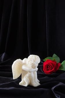 Eine kerze in form eines engels mit flügeln und einer roten rose auf einem schwarzen tuch