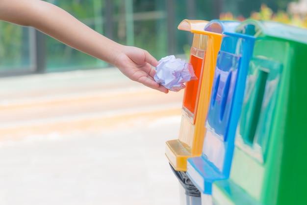Eine kinderhand, die zerknittertes papier im papierkorb wirft. weltumwelttag konzept.