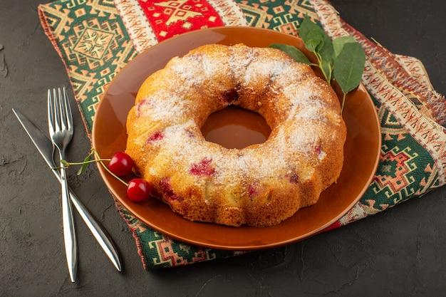 Eine kirschkuchenrunde der draufsicht gebildet innerhalb der braunen platte auf dem dunklen schreibtischkuchenkekszuckersüß