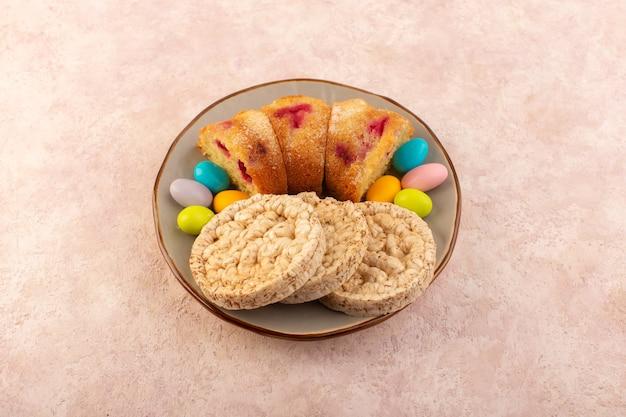 Eine kirschkuchenscheibe von oben mit süßigkeiten und keksen auf dem hellrosa schreibtischkuchenkekszuckersüß