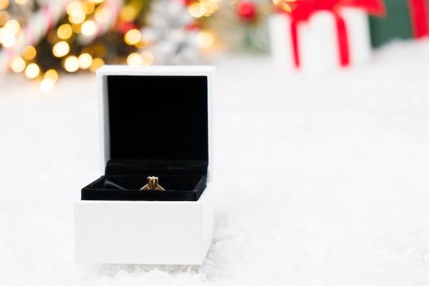 Eine kiste mit goldenem ring auf dem schnee