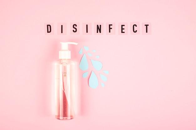 Eine klare flasche mit einem desinfektionsgerät, aus dem blaue tropfen mit dem wort desinfektion auf rosa fließen.