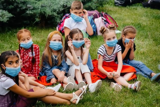 Eine klasse maskierter schulkinder trainiert während der epidemie im freien. zurück in die schule, lernen während der pandemie.