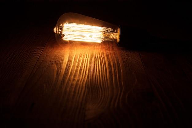 Eine klassische edison-glühbirne auf hölzernem hintergrund eingeschaltet. retro edison glühbirne