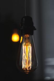 Eine klassische edison-glühlampe auf dunkelheit