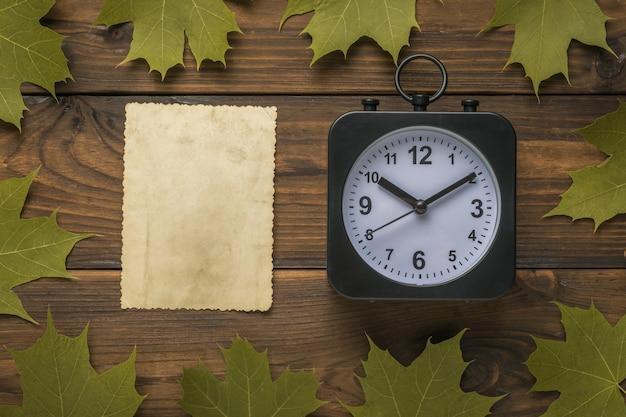 Eine klassische uhr und ein blatt antikes papier in einem ahornblattrahmen auf einem hölzernen hintergrund.
