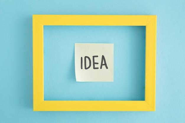 Eine klebrige anmerkung der idee mit gelber grenze über dem blauen hintergrund