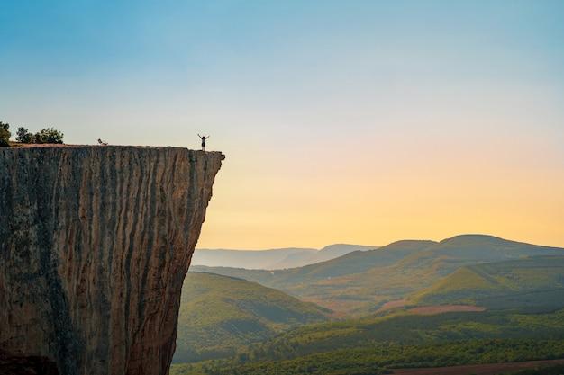 Eine kleine figur eines touristen mit offenen armen, der am rand einer klippe in den sommerbergen steht