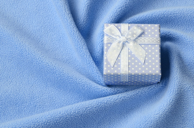 Eine kleine geschenkbox in blau mit einer kleinen schleife liegt auf einer decke aus weichem und pelzigem hellblauem fleece.
