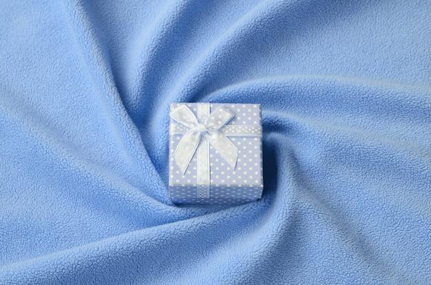 Eine kleine geschenkbox in blau mit kleiner schleife liegt auf einer decke