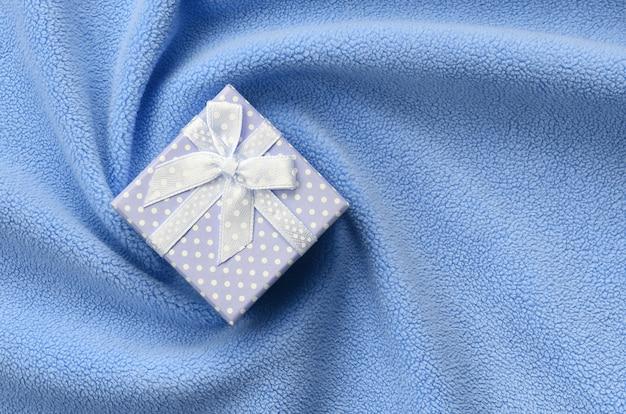 Eine kleine geschenkbox in blau mit kleiner schleife liegt auf einer weichen decke