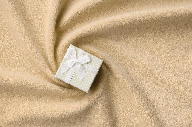 Eine kleine geschenkbox in orange mit einer kleinen schleife liegt auf einer decke aus weichem und pelzigem hellorangenem fleece