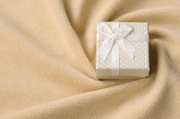 Eine kleine geschenkbox in orange mit kleiner schleife liegt auf einer decke aus weichem und pelzigem hellorangeem fleece mit vielen relieffalten.